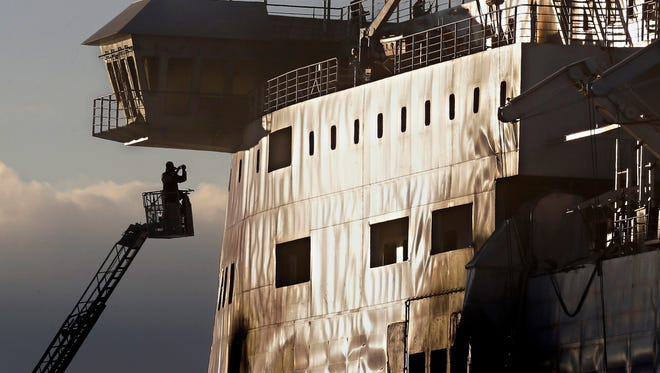 A fireman works outside the Norman Atlantic ferry after that has been towed into the port of Brindisi, southern Italy, Friday, Jan. 2, 2015. The blaze that broke out Sunday and torched the ferry has killed at least 11 people and authorities prepared to search it for possible more dead. Italy says 477 people were rescued, most by helicopters that plucked survivors off the top deck in gale-force winds and carried them to nearby boats.