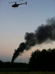 A helicopter flies of the still-smoking crash site