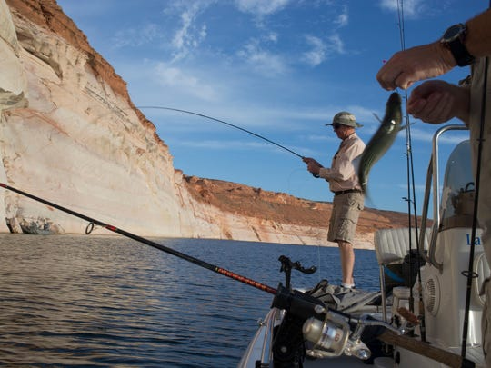 Lake Powell fishing guide, Kevin Campbell, left, and George Vest  fish for striped bass near Glen Canyon Dam.
