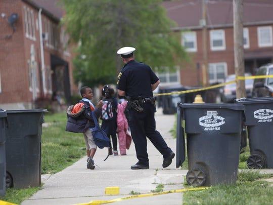 Kids fresh off the school bus walk past shooting scene in Winton Hills May 14.