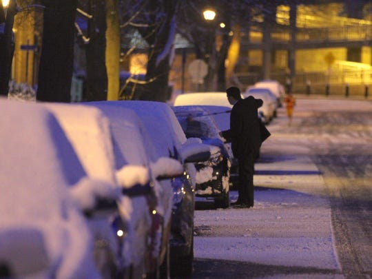 Corey Ernisse brushes snow off his car after a dusting last year.
