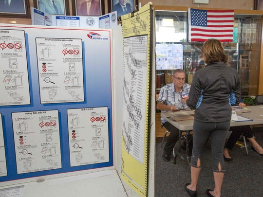 The inside of a voting booth can be seen with instructions in several languages as a poll worker works with a voter at a polling station in San Diego, Calif., on June 7.