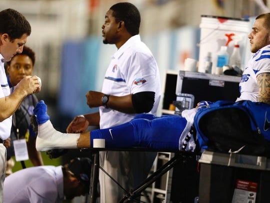 Memphis athletic trainer Darrell Turner, left, tapes quarterback Riley Ferguson's ankle during the Boca Raton Bowl on December 20, 2016.