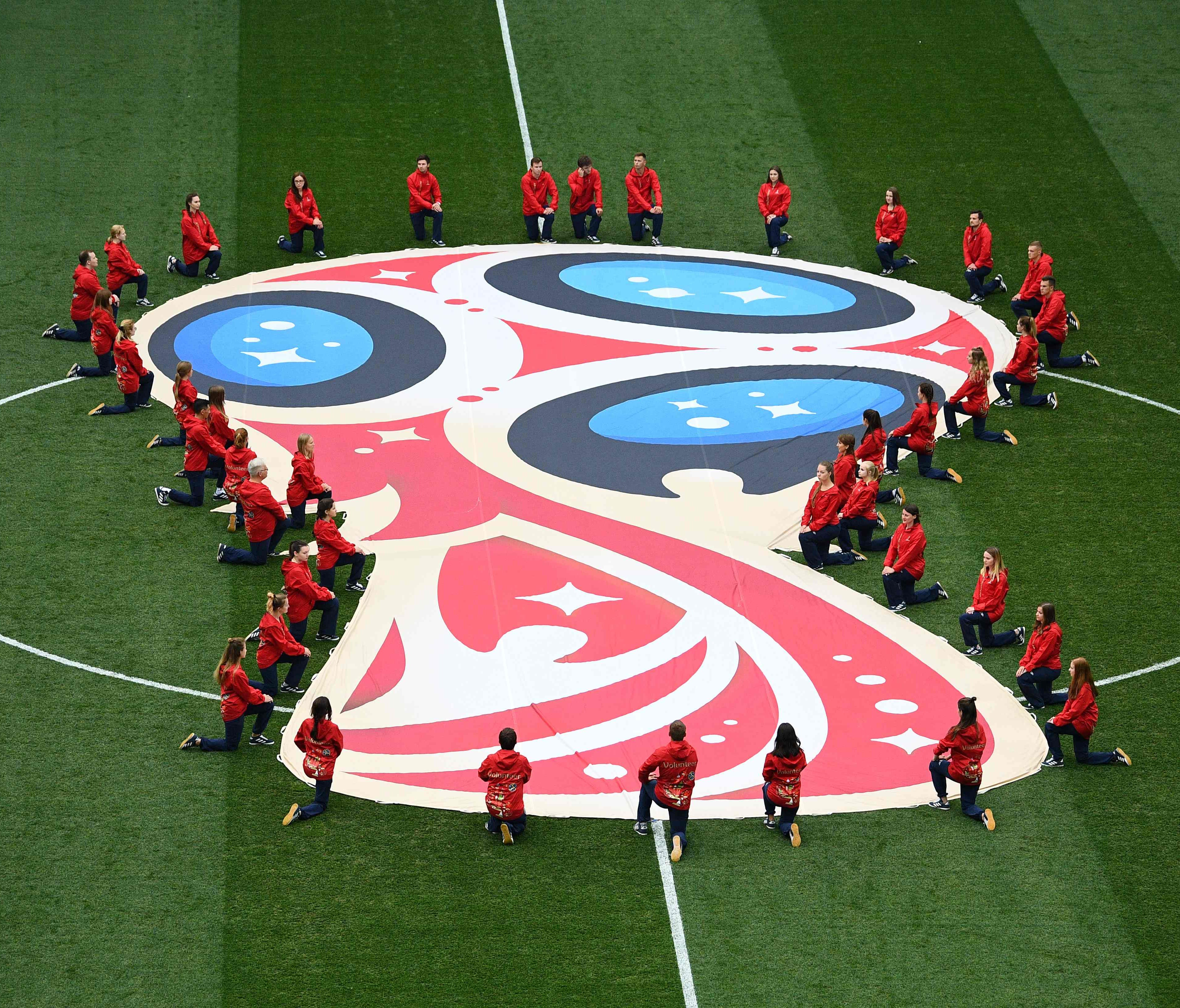 Volunteers kneel next to the logo of the Russia 2018 World Cup.