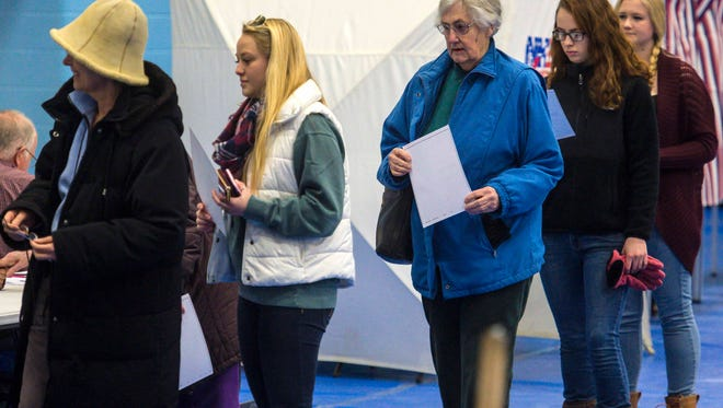Women line up to submit their marked ballots at Oyster River High School in Durham, New Hampshire on Tuesday, February 9, 2016.