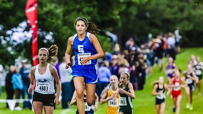 Stephanie Vanis (center) and the East Lansing girls own the top spot in this week's Lansing area coaches cross country poll.
