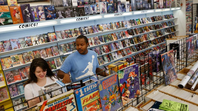 Arizona Dyer and Brent Williams, of Wilmington, peruse comics at The Comic Book Shop in Brandywine Hundred on Thursday. Digital comics sales jumped to $100 million in 2014, but fell to $90 million last year.