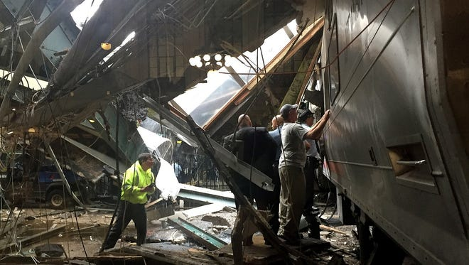 Train personnel survey the NJ Transit train that crashed into the platform at the Hoboken Terminal on Sept. 29, 2016, in Hoboken, N.J.