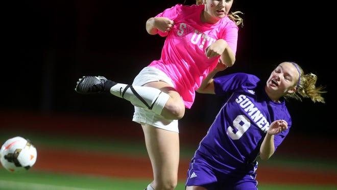 South Kitsap player Savannah Foster, left, deflects the ball past Sumner's,Sam Larberg Thursday night at South Kitsap High School.