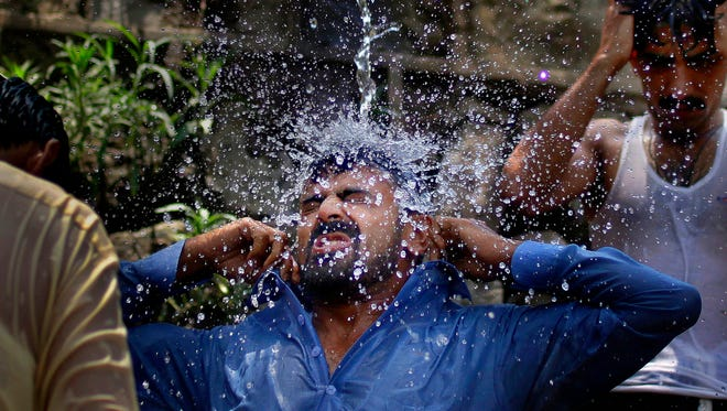 A Pakistani man cools himself off under a water supply to beat the heat during the holy fasting month of Ramadan, in Islamabad, Pakistan, Tuesday, June 7, 2016.