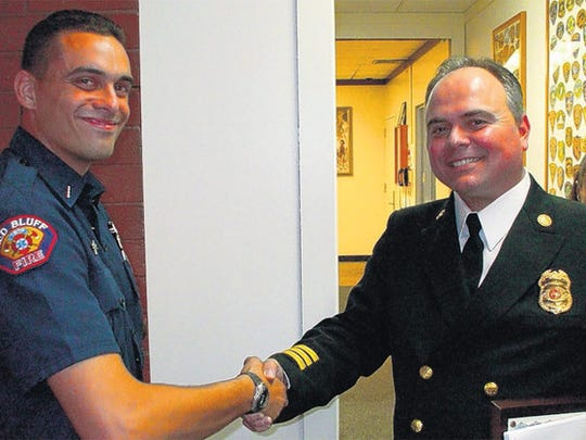 In 2008, Red Bluff Firefighter of the Year Matthew Shobash, left, gets a handshake from outgoing Fire Chief Gerry Gray before Tuesday night's City Council meeting.