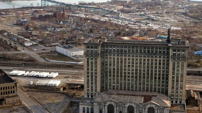 The massive abandoned and vacant Michigan Central Railroad depot rises above the landscape of southwest Detroit with the Ambassador Bridge at the back left.