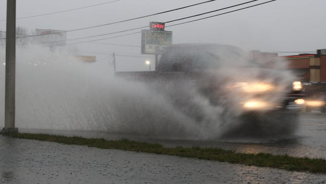A truck drives through a deep puddle on Riverside Drive during heavy rains on Thursday.