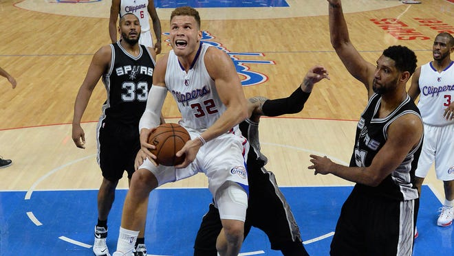 Los Angeles Clippers forward Blake Griffin (32) battles San Antonio Spurs forward Tim Duncan (21) for a rebound in the first half of game seven of the first round of the NBA Playoffs at Staples Center.