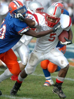 Vineland running back Tony Loatman tries to stiff arm his way out of Millville outside linebacker Dante Broughton's pressure during the Fighting Clan's win on Thanksgiving.