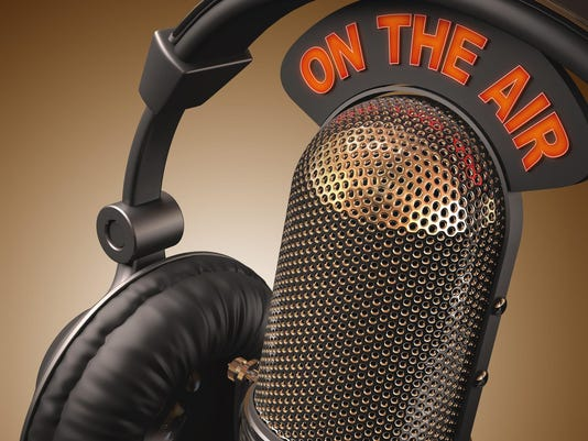 Close up of microphone and headphones with On The Air sign
