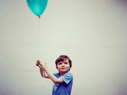 Petit garçon souriant et tenant un ballon