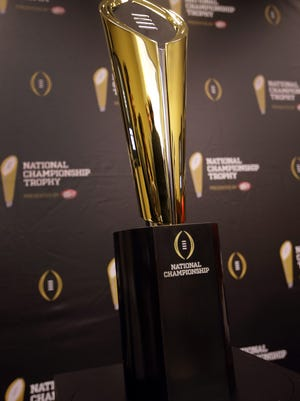 This photo shows the College Football Playoff National Championship Trophy in Irving. A rising gold football-shaped trophy will be the prize for the national champion in the new College Football Playoff.