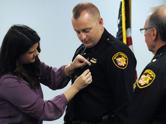 Vanessa Warner pins a sergeant's badge onto her husband