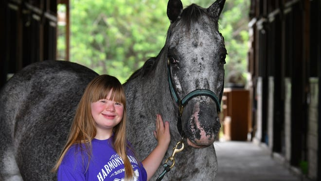 Nicole Suchyna with Shy Ann, one of the horses of Harmony Farms in Cocoa, dedicated to helping disabled people through interactions with horses.
