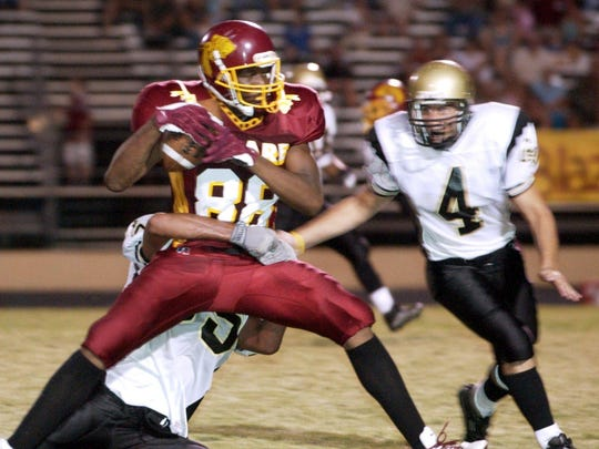 Tulare Union's Virgil Green (88) holds onto possession during the first half of a high school football game at Bob Mathias Stadium on Sept. 10, 2004.