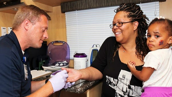 Keith Hickerson, left, the emergency medical technician on Saint Thomas Rutherford Hospital's Mobile Health Unit, performs a free health exam at the Back-to-School Bash in Smyrna on Aug. 3, 2014.