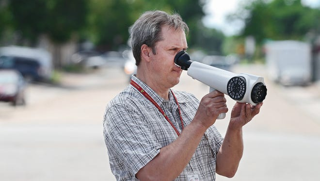 """Ben Siller, an environmental protection investigator in Denver's Department of Environmental Health, uses a """"Nasal Ranger"""" to discern odorous air while investigating odor complaints around the city on Friday, Aug. 8, 2014."""