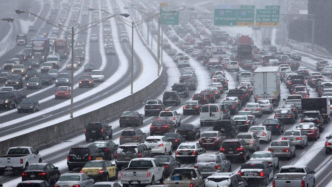 Traffic inches along the connector of Interstate's 75 and 85 as snow blankets Metro Atlanta on Tuesday afternoon.