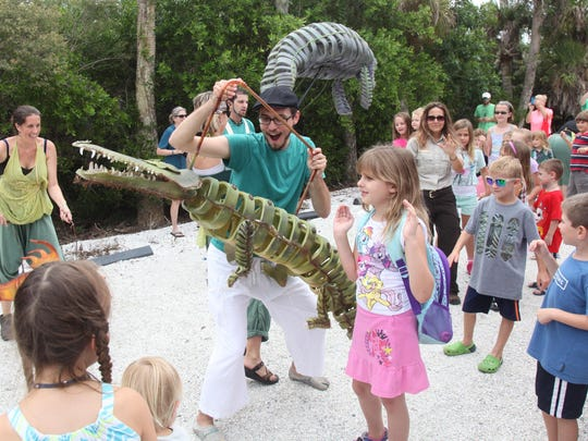 "Nick Augustine, of IBEX Puppetry, entertains children with his crocodile puppet during ""Ding"" Darling Days."