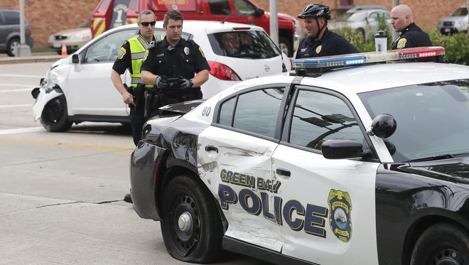 Green Bay Police Department officers investigate a crash involving a police car at the corner of North Webster Street and University Avenue on Friday. The officer involved in the crash was taken to a hospital.