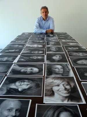 Photographer Peter Freed poses in his Rye studio with the black and white portraits he took of women aged 35 to 104 for a book he is working on.