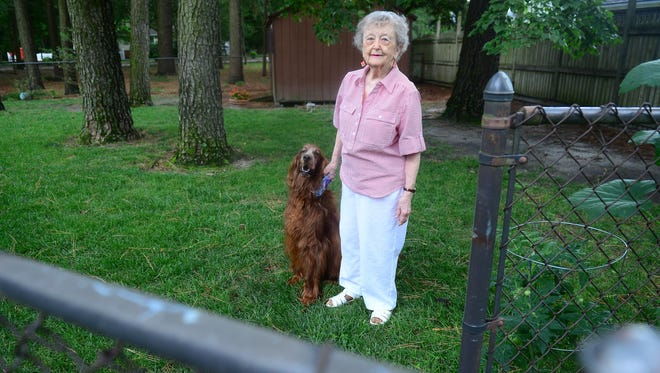 Barbara Schultz and her English Irish Setter, Duchess, pose for a photo in their backyard on Friday, July 7, 2017, surrounded by a chain link fence.