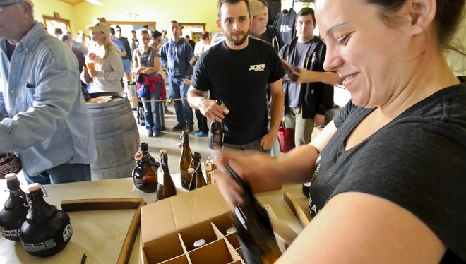 Kerrie Montgomery fills a customer's order at Hill Farmstead Brewery in Greensboro on Friday, August 15, 2014.