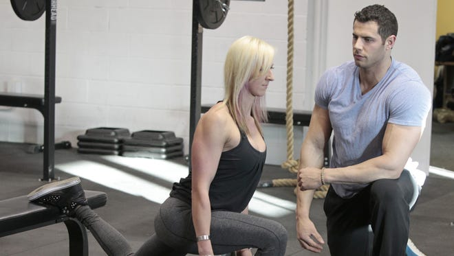 """Kyle Glickman, a national fitness model who just started his own personal training business, Glickfit, works with client Ewa Hlebowicz, reminding her to keep her chin up while doing """"rear foot elevated split squats"""" at The Training Grounds in Henrietta."""