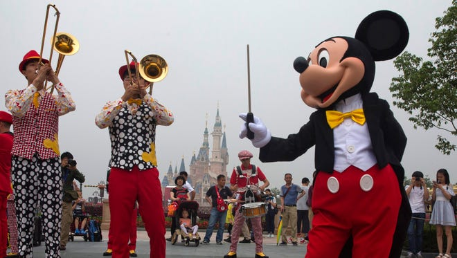 Mickey Mouse entertains visitors on the opening day of the Disney Resort in Shanghai, China, Thursday, June 16, 2016. Walt Disney Co. opened its first theme park in mainland China on Thursday at a ceremony that mixed speeches by Communist Party officials, a Chinese children's choir and actors dressed as Sleeping Beauty and other Disney characters. (AP Photo/Ng Han Guan)