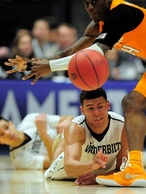 Vanderbilt guard Wade Baldwin (4) battles with Tennessee guard Devon Baulkman (34) for a loose ball in the second round of the SEC Tournament on March 10, 2016 at Bridgestone Arena.