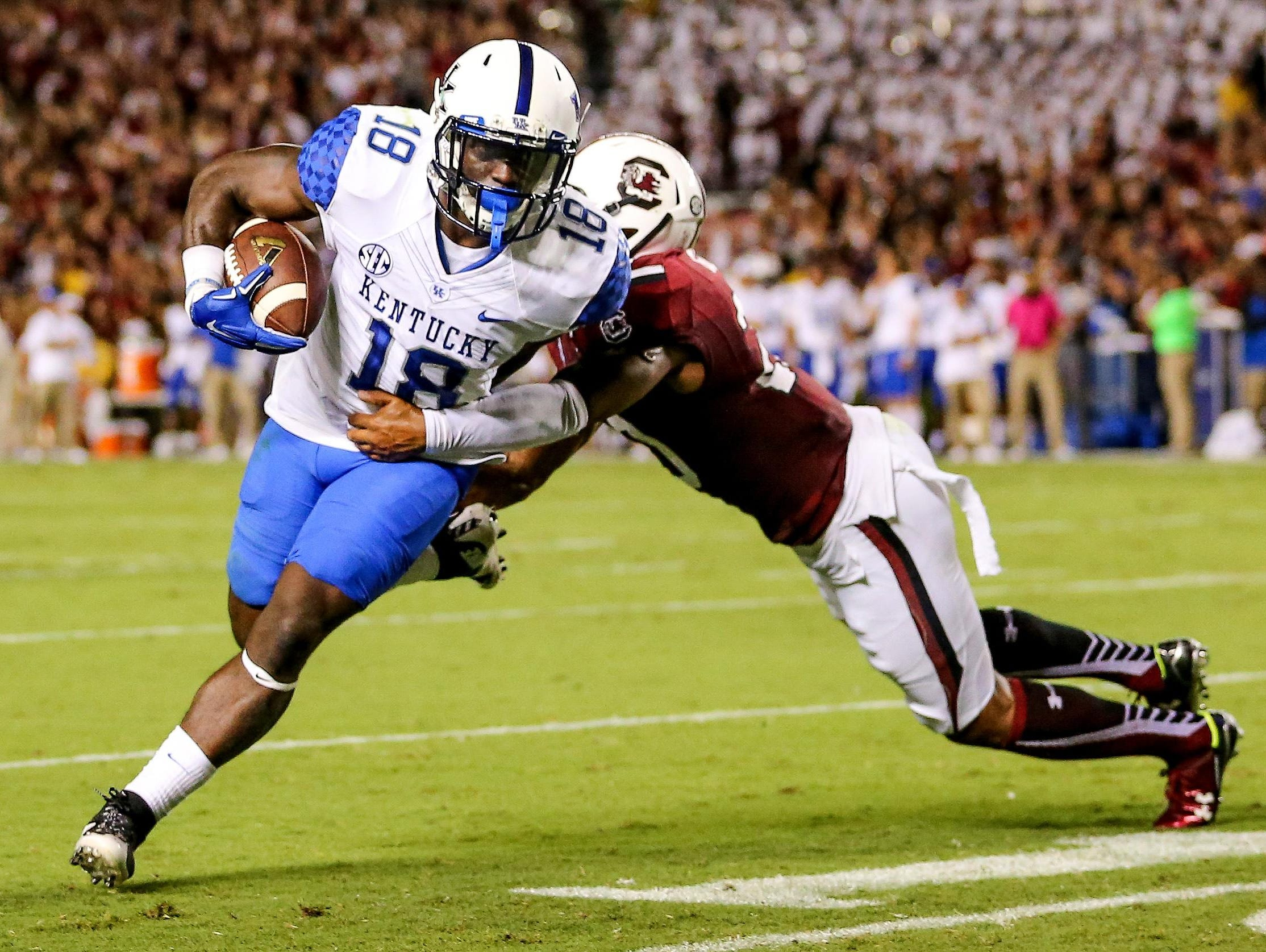 Sep 12, 2015; Columbia, SC, USA; Kentucky Wildcats running back Stanley Williams (18) runs towards a first down stopped by South Carolina Gamecocks safety T.J. Gurley (20) during the second quarter at Williams-Brice Stadium.
