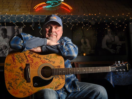 Songwriter Kent Blazy holds the guitar with the signatures