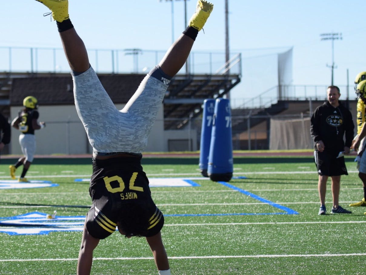 Mount Vernon standout and Iowa offensive lineman signee Tristan Wirfs does a handstand during a January practice for the US Army All American Bowl in San Antonio.