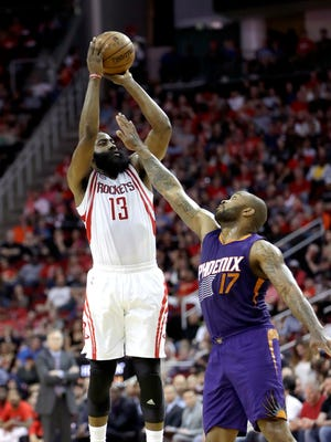 Houston Rockets' James Harden (13) shoots as Phoenix Suns' P.J. Tucker (17) defends during the first half of an NBA basketball game, Saturday, Feb. 11, 2017, in Houston.