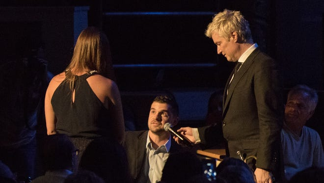 Jordan Hernandez pops the questions to Samantha Major with Chris Botti holding a microphone for the 2,000 people listening to the wedding proposal during the Xerox Rochester International Jazz Festival.