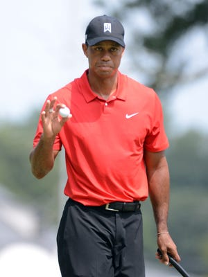 Tiger Woods acknowledges the crowd after a par on the 1st hole during the final round of the Wyndham Championship golf tournament at Sedgefield Country Club.