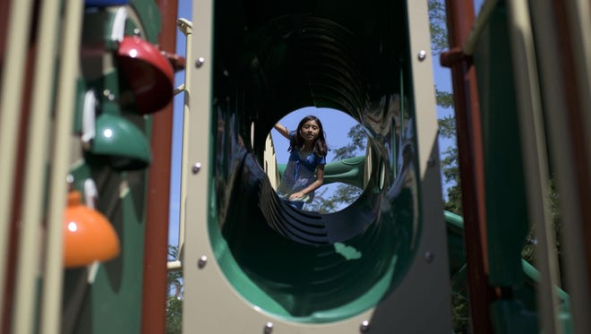Karen Rodriguez, 8, heads into a tunnel at the newly revitalized Johnson Reeves Playground on Friday.
