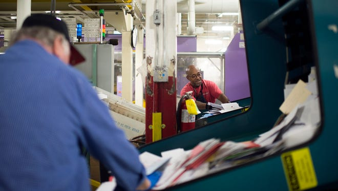 Wallace Brooks Jr., right, sorts through a bin of mail inside the USPS sorting facility Tuesday, Dec. 15 in Bellmawr.