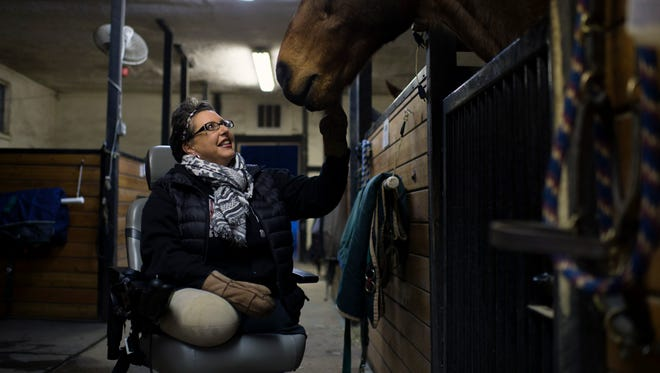 Riverside resident Tina Elliott pets her horse, Woody, inside his barn in Moorestown. The 43-year-old lost her legs last year, due to complications of severe sepsis.