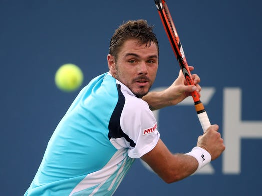 Stanislas Wawrinka (SUI) returns a shot to Tommy Robredo (ESP) on day eight of the 2014 U.S. Open.