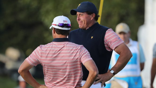 Phil Mickelson and Kevin Kisner celebrate after Mickelson made a putt on the 18th hole during the second round four-ball matches of The President's Cup golf tournament at Liberty National Golf Course.