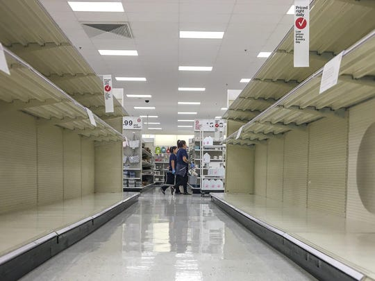 Two people walk by empty toilet paper shelves at the Glenwood Meadows Target in Glenwood Springs, Colo on Tuesday, March 17, 2020. (Chelsea Self / Glenwood Springs Post Independent via AP)