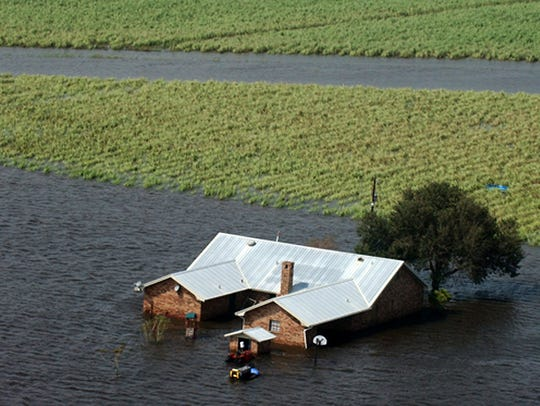 A flooded home and sugar cane field near Henry, La.,