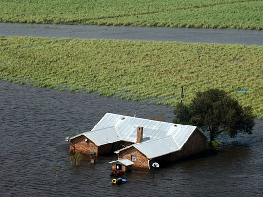 A flooded home and sugar cane field near Henry, La., after Hurricane Rita.
